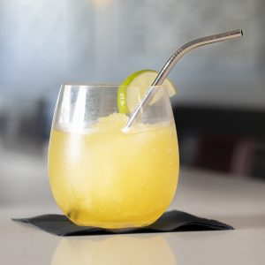 "5.75"" bent cocktail stainless steel straw on a napkin on a table in a restaurant"