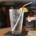 "9"" bent stainless steel straw in glass of ice water"