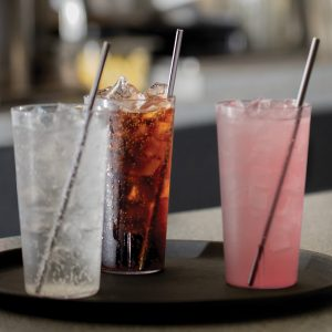 "9"" Straight Stainless Steel Straws in various drinks on a serving tray at a restaurant"